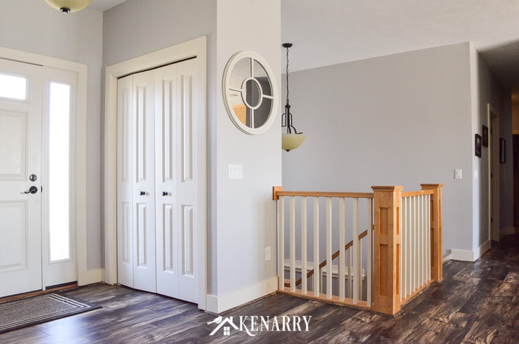 Front entryway in an open concept living room, the top of a staircase with natural maple newel posts