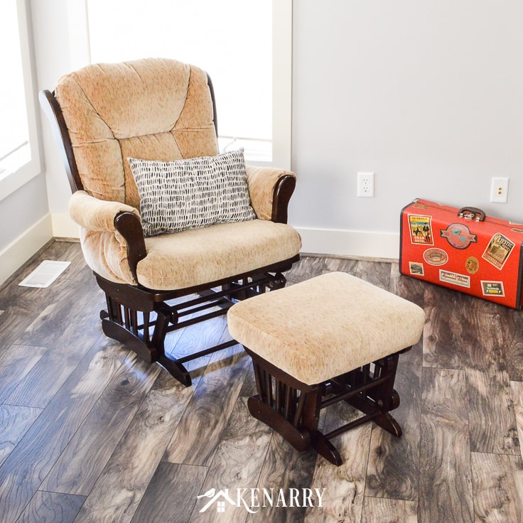 Tan glider rocker with espresso wood in a living room next to a vintage suitcase