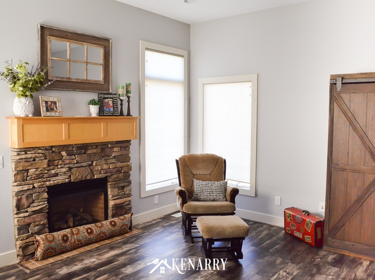 Stone fireplace with natural maple mantel, tan glider rocker