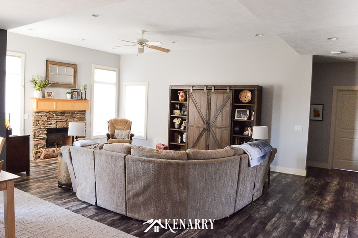 The back of a tan sectional sofa in a farmhouse style living room