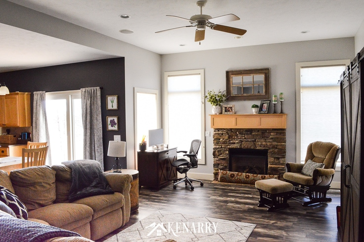 Farmhouse style living room with a computer desk and stone fireplace with natural maple mantel