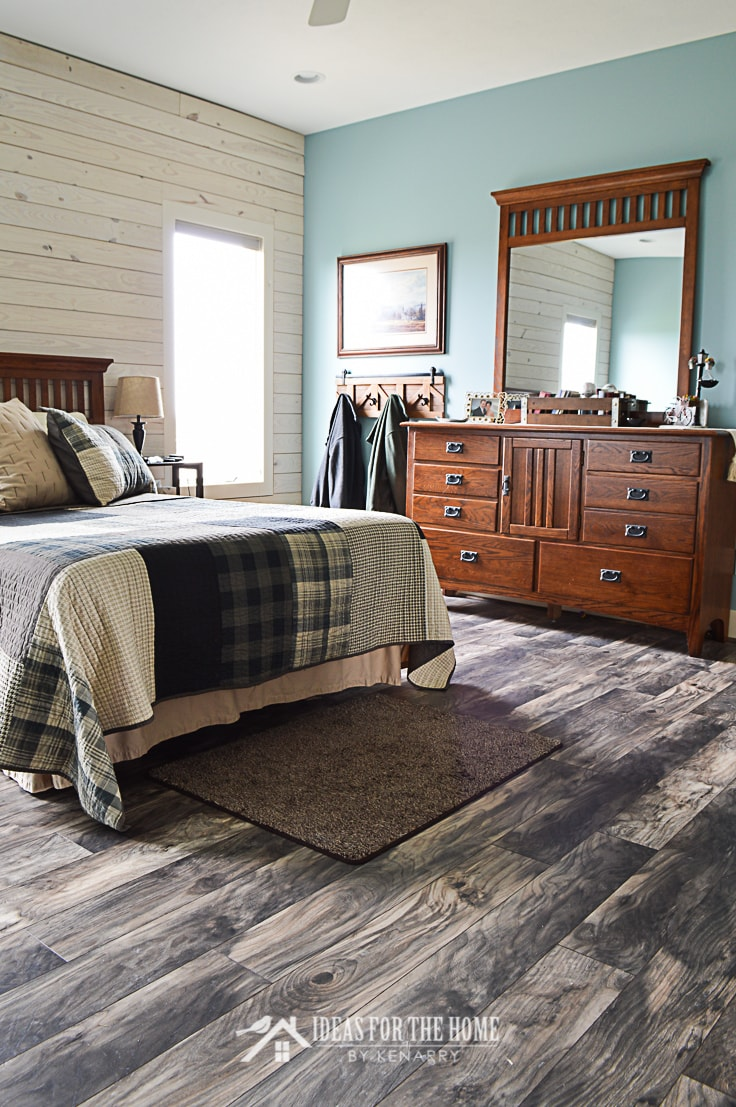 Allen + Roth Chesterfield Hackberry laminate flooring from Lowe's in a master bedroom with a queen sized bed and a large dresser with a mirror