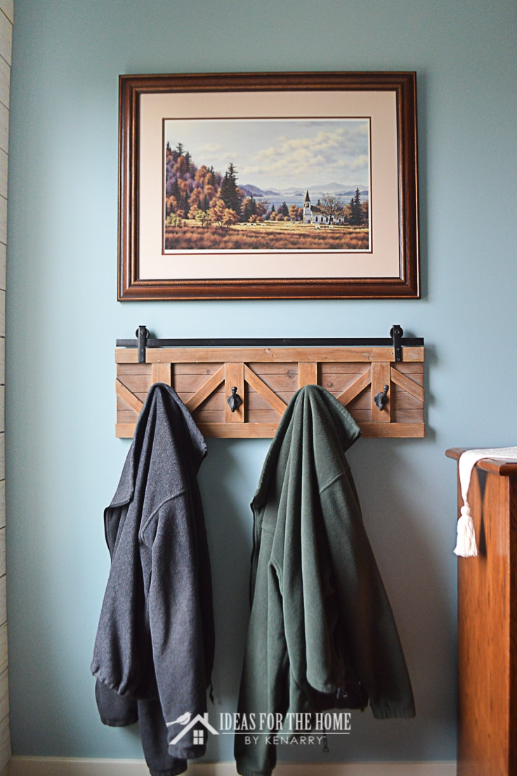 A painting above a farmhouse style rack with hooks in a master bedroom