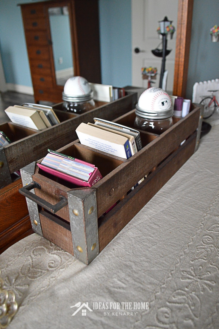 Close up of a farmhouse style wooden box and cloth runner on top of a dresser in a bedroom