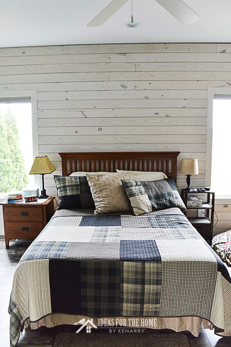 A queen size bed with a Woolrich Winter Hills Plaid Quilt Set in a master bedroom