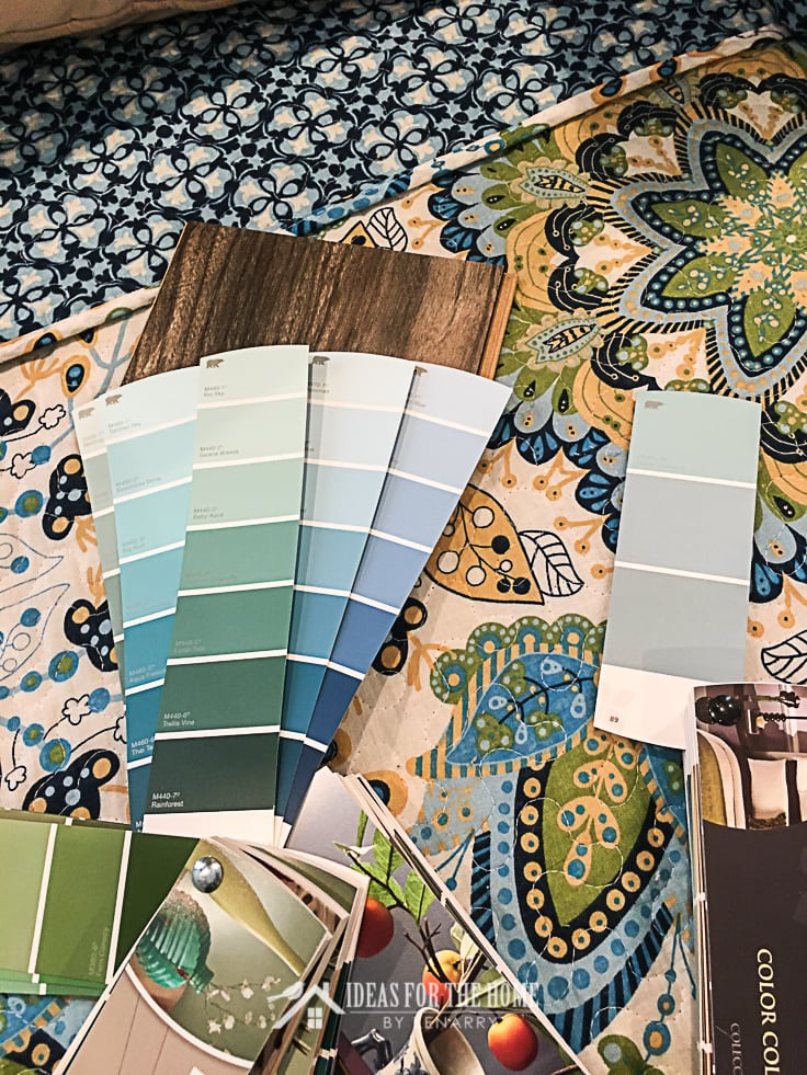 Paint swatch books fanned out on a bed in a master bedroom