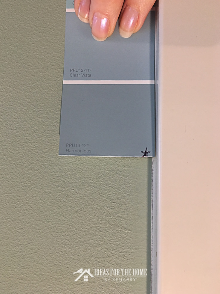 Harmonious paint swatch from Behr paint being held up on the wall to show the difference in wall color