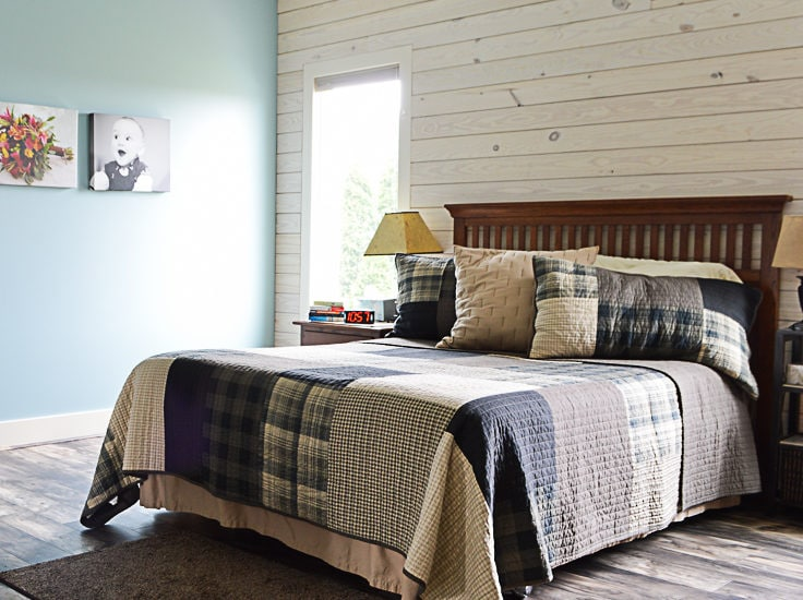 Queen sized bed with a Woolrich quilt in a master bedroom