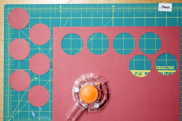 red paper with six holes cut out beside a circle cutter