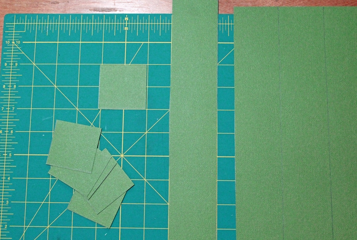 a pile of green squares beside a piece of green scrapbook paper on a cutting mat