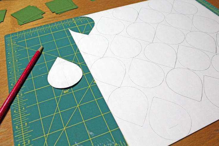 white teardrop on a cutting mat next to a paper with several teardrops drawn