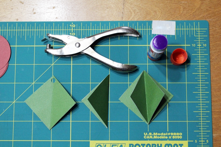 green squares demonstrating the steps to punch a hole, fold in half, and glue together
