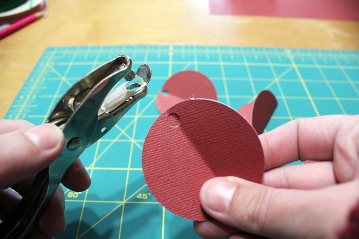using a hole punch to make a hole in a circle