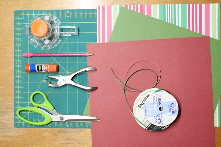 scrapbook paper, ribbon, scissors, a hole punch, glue, and a paper punch on a rubber cutting mat