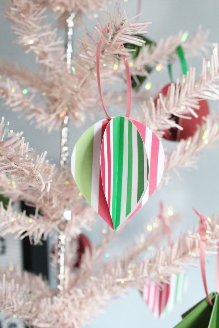 closeup of a teardrop ornament made from red, pink, and green striped paper on a pink tree