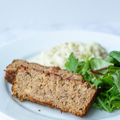 Two slices of meatloaf made from ground turkey on a plate with mashed potatoes and salad