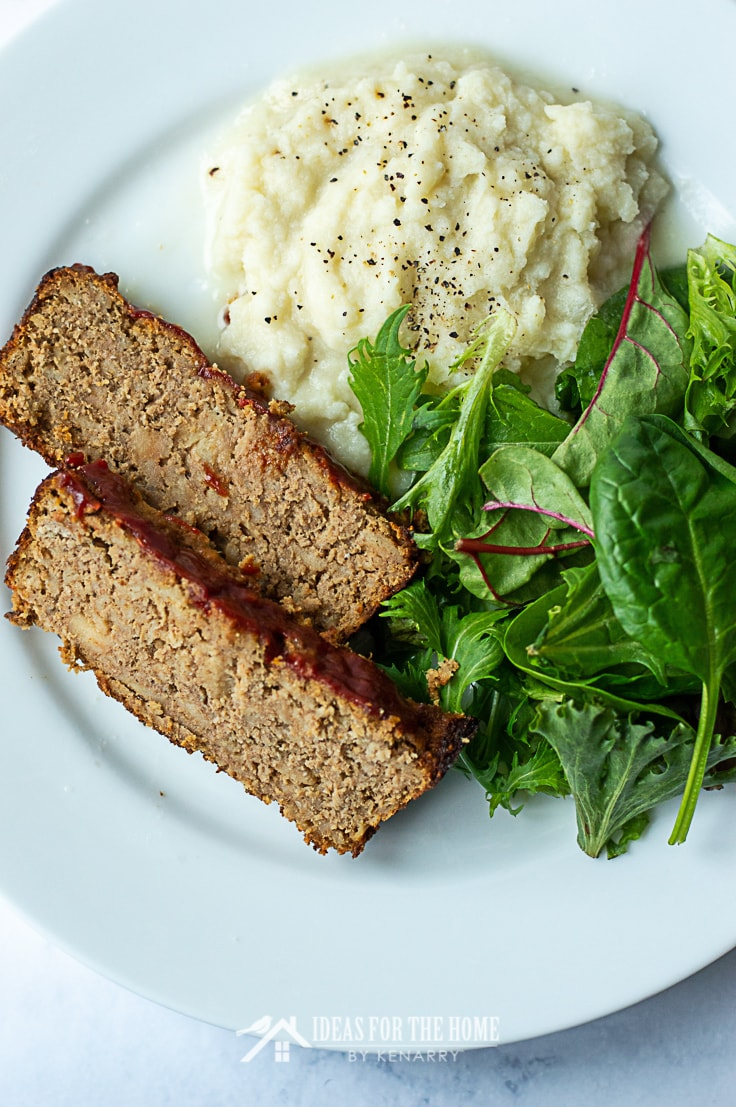 Overhead image of two slices of meatloaf made from ground turkey alongside mashed potatoes and salad on a plate