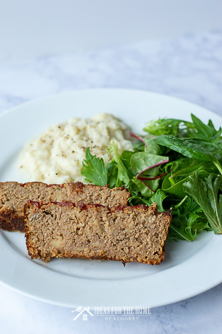 Two slices of delicious turkey meatloaf topped with barbecue sauce on a plate with mashed potatoes and a side salad