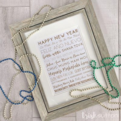 Framed New Year printable with beads on a wood background.