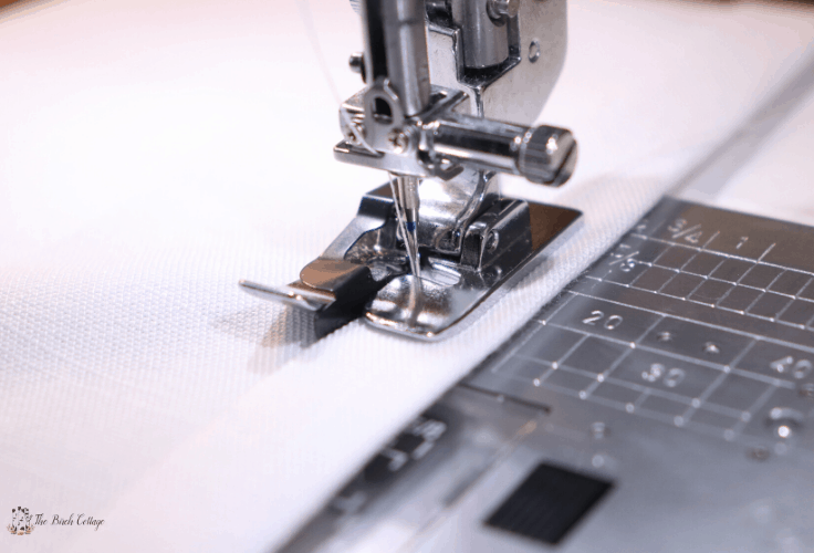 Use an edger foot on the sewing machine to sew the hems.
