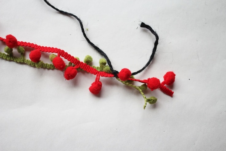 Red and green pom pom fringe tied together with black twine