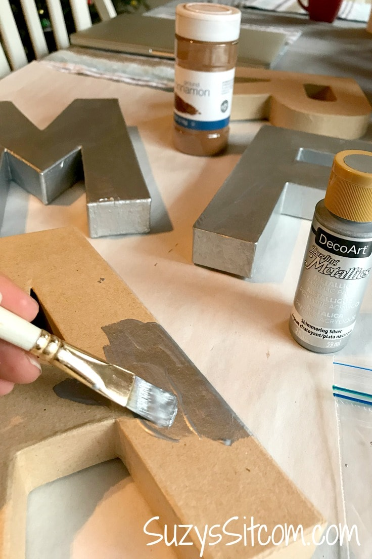 Cinnamon, cardboard letters, and silver metallic paint.