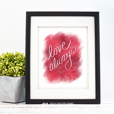 Love Always Valentine's Day print in a black frame next to a small potted plant