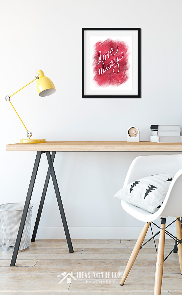 Framed Valentine's Day art hanging above a modern style desk