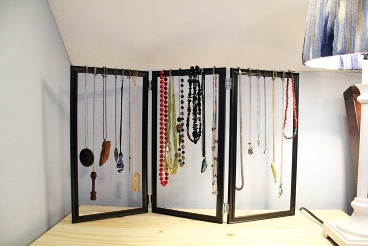 the jewelry organizer sits on a nightstand and a dozen necklaces hang from the top of the frames