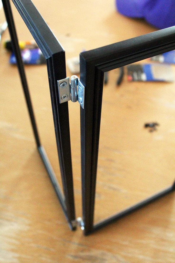two frames attached by hinges stand at a right angle on a wooden table