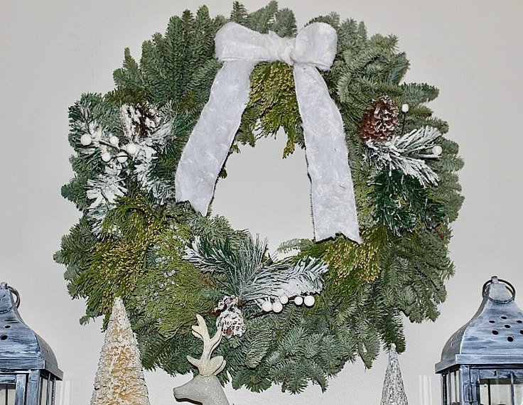 fresh pine winter wreath hanging above mantel