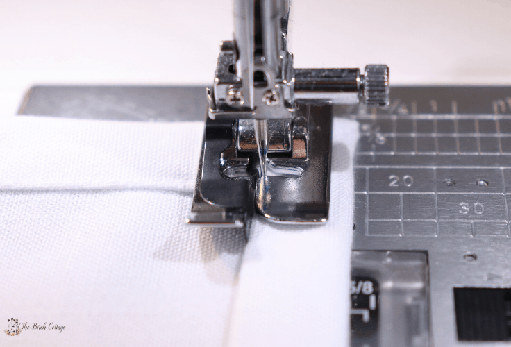A close-up of an edger foot on a sewing machine sewing a mitered corner.