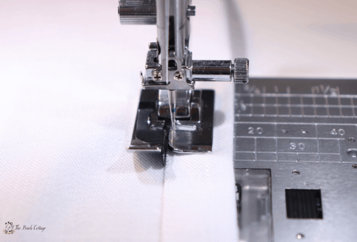 A close up of an edger foot on a sewing machine sewing a hem.