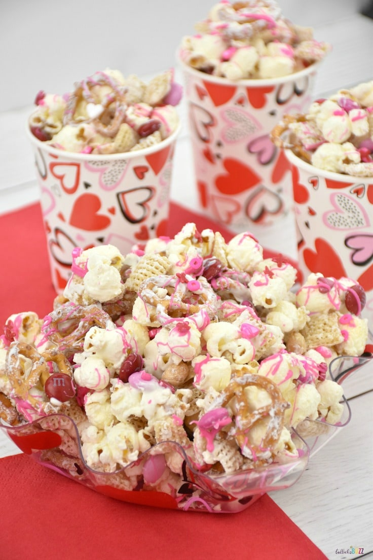 This salty and sweet Valentine's Day snack mix is made with crispy cereal, crunchy pretzels, chocolaty candies, and salty peanuts all drizzled with melted chocolate and dusted with pink, red, and white sprinkles!