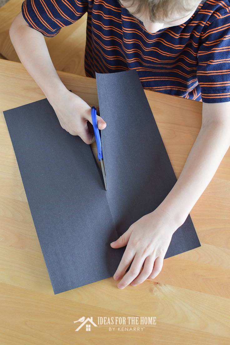 Child cutting black construction paper in half vertically with scissors