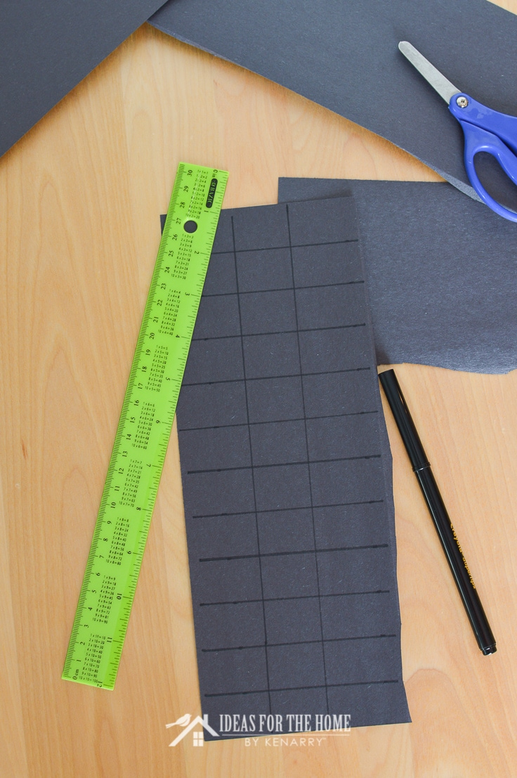 Ruler measuring black construction paper into equal sections to make into spider legs for a craft