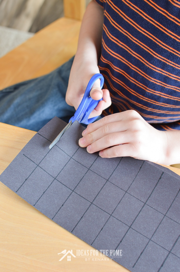 Boy cutting black construction paper to make into spider legs for a kids craft project for Halloween or Valentine's Day