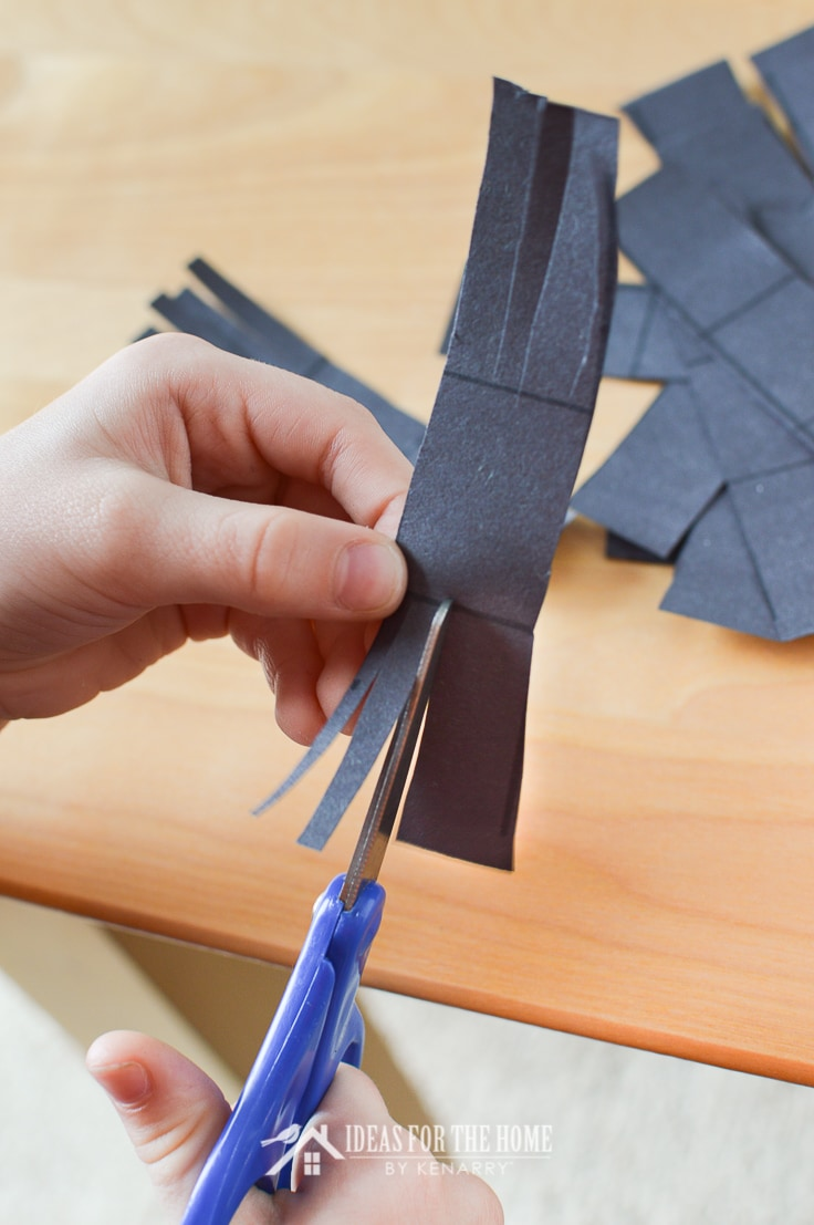 Child cutting fringe in black construction paper to make legs for candy spiders