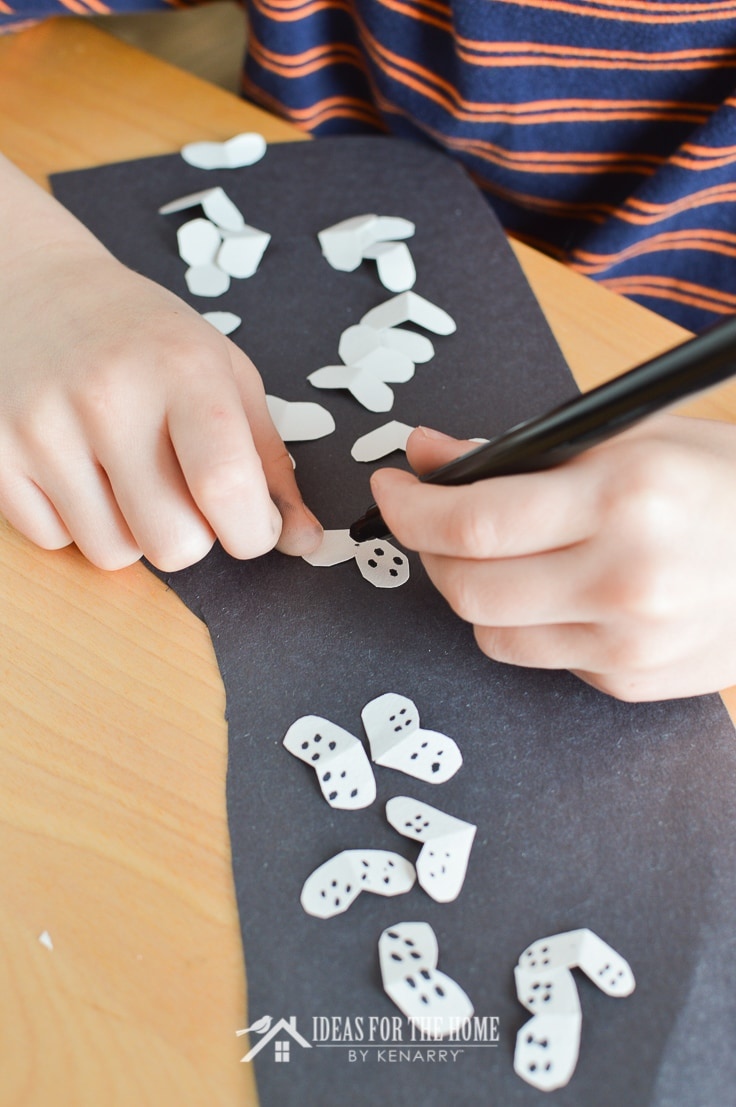 Boy using a black marker to make dotted eyes as part of a spider craft