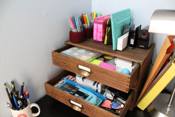 messy drawers stuffed with odd office supplies, with more supplies stacked on top of the drawers