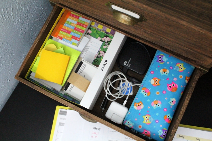 an organized wooden drawer showing paper drawer organizers to separate notepads, electronics and a zip bag
