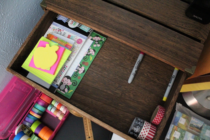 a wooden drawer with paper, pens, and washi tape laid out to mark where dividers will go