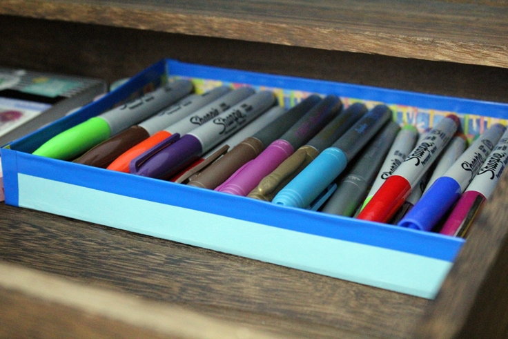 a blue paper drawer organizer filled with Sharpie pens and markers