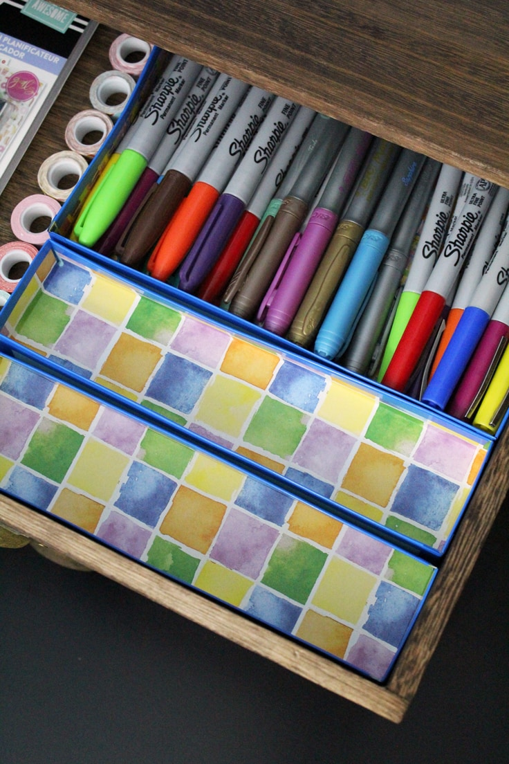 3 small paper drawer organizers, one filled with pens and markers