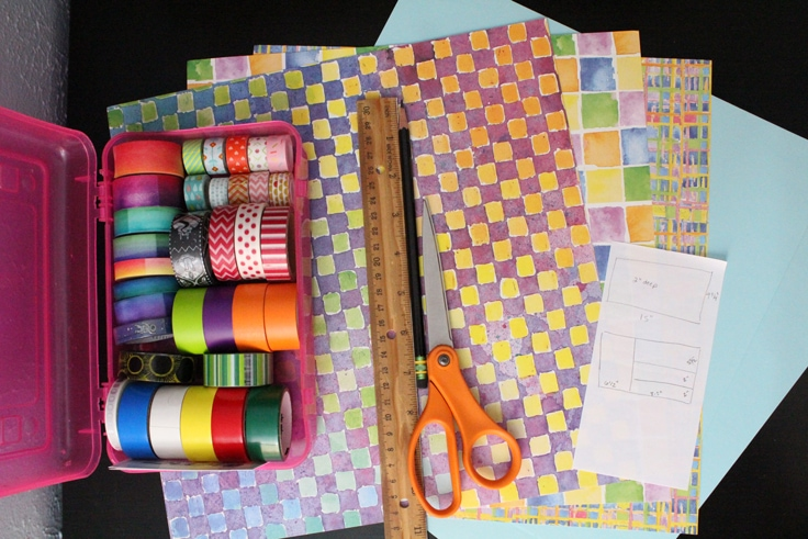 a pink box of washi tape, a ruler, scissors, and several pieces of scrapbook paper