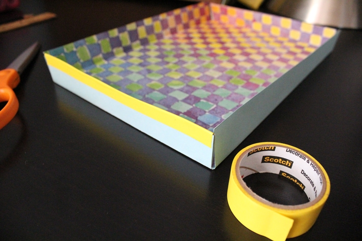 a blue paper drawer box lined with yellow tape