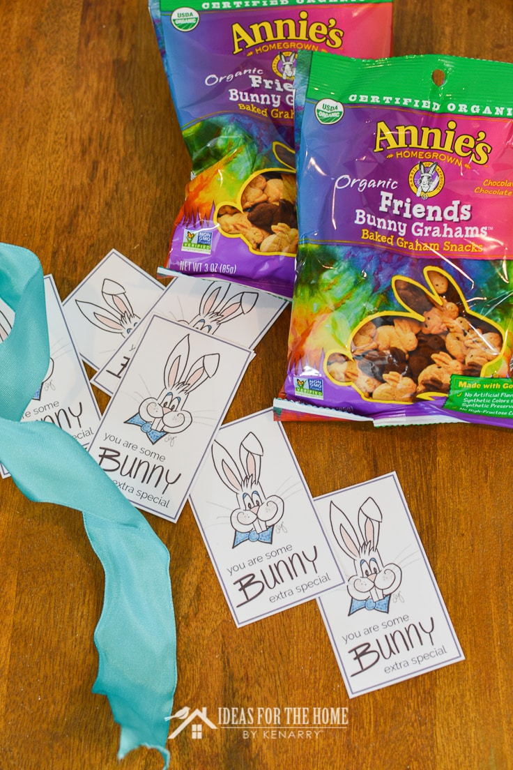 Easter gift tags laying on a table top next to Annie's Organic Bunny Grahams