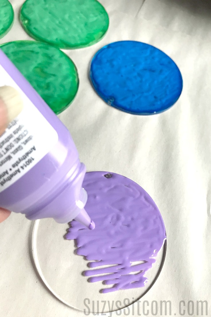 Purple stained glass paint being poured onto a clear plastic disk.