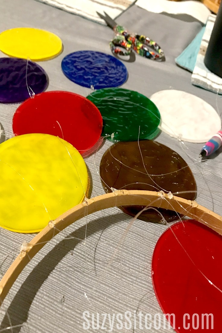An embroidery hoop with painted acrylic disks tied to it