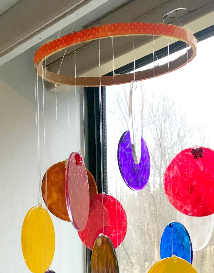 A DIY sun catcher hanging from the ceiling in front of a window